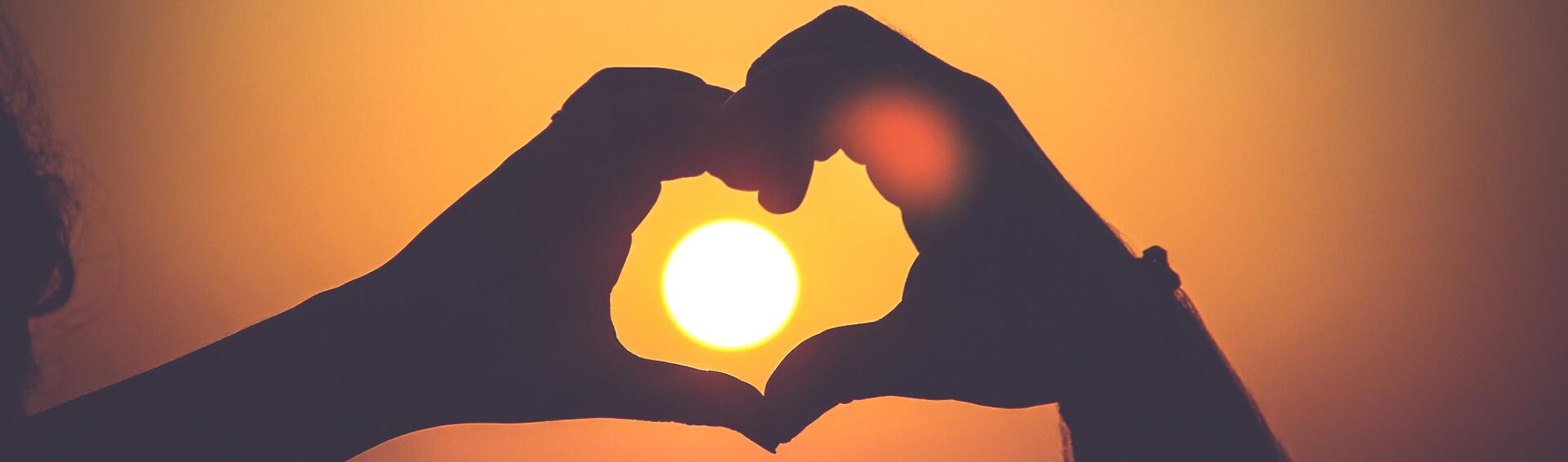 Coeur avec les mains devant un coucher de soleil